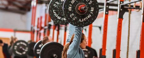 Gemma performing a strict press in a CrossFit class